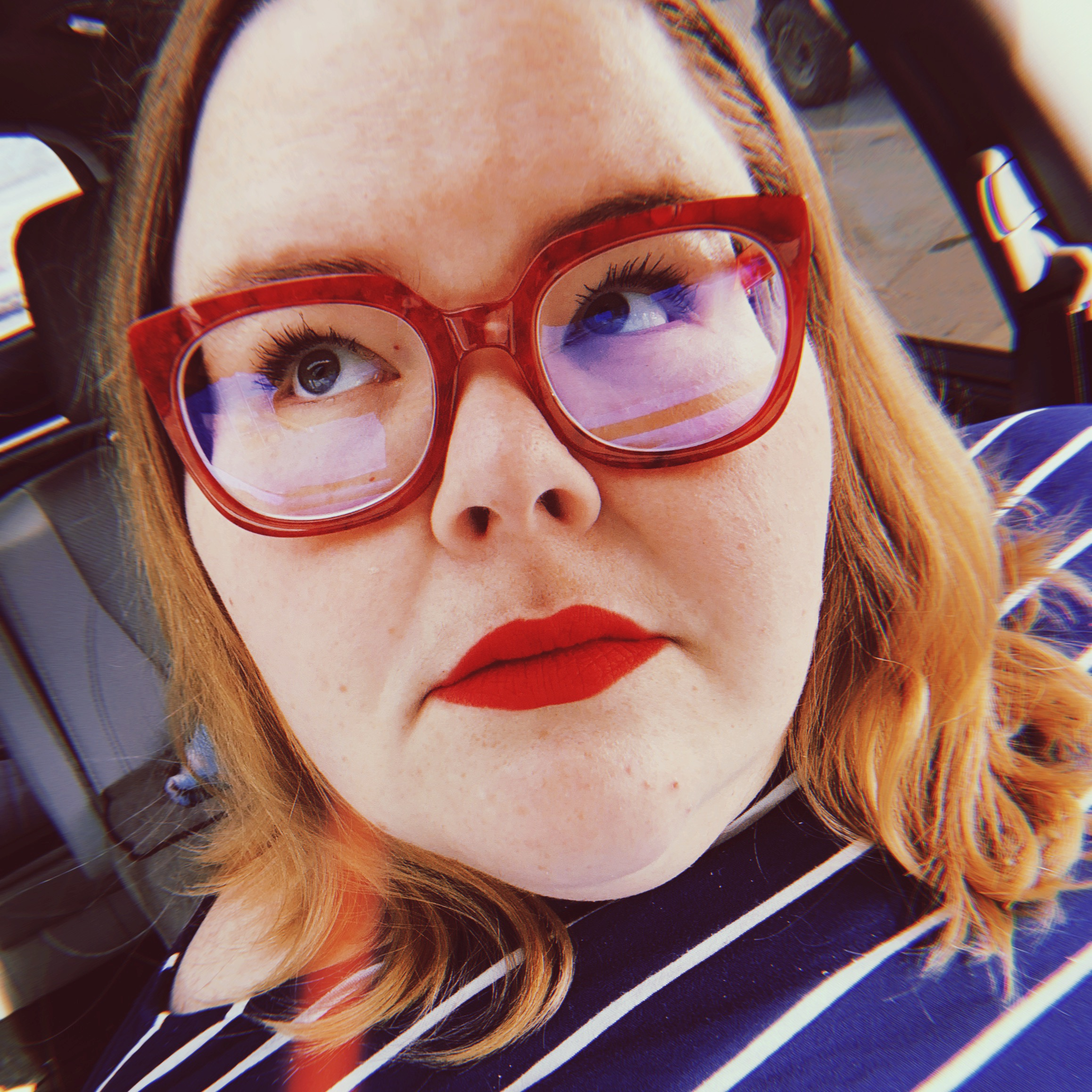 a fat white person wearing large thick-rimmed red glasses and red lipstick